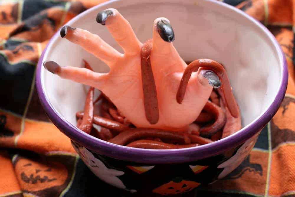 A large hand popping out of Halloween bowl covered in Halloween hot dogs