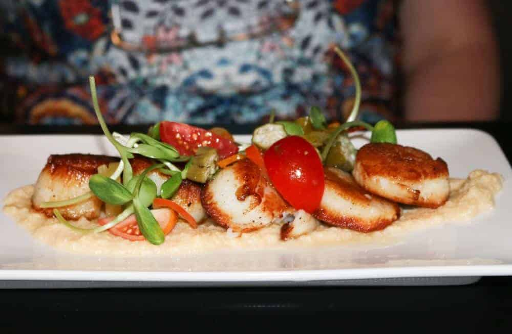 SCALLOPS: pan seared and served with fresh corn polenta, pickled okra and peppers, locally grown shoots, and cherry tomatoes