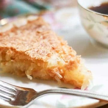 This French Coconut Pie Recipe has a crackly, sugary crust with a wonderfully gooey vanilla and coconut center. It is so sinfully good that it really should be illegal.