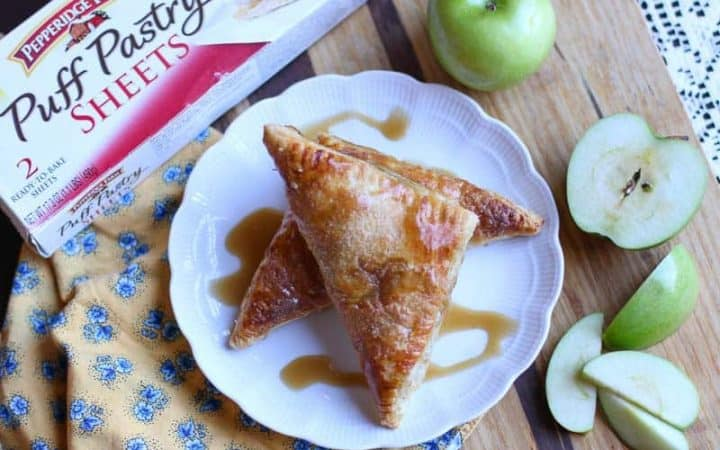 apple turnovers on a white plate surrounded by granny smith apples