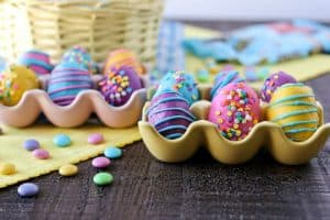 Cookie Dough Easter Eggs with M&M'S® from Certified Pastry Aficionado: Chewy edible chocolate chip cookie dough truffles with M&M'S® milk chocolate candies, rolled into egg shapes, and dipped into fun colored candy melts to make them look like Easter eggs.