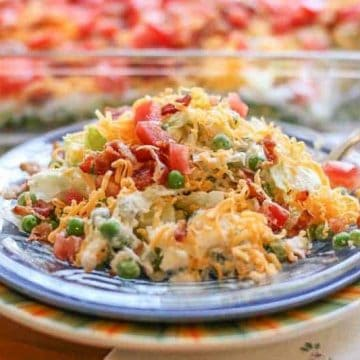 Layered Salads are big hit for parties, cookouts, and family gatherings. This Easy Layered Salad Recipe is my favorite. This recipe has bacon, cheddar cheese, and parmesan, combined with bell pepper, peas, tomatoes, onions, and lettuce. The combination is delicious! This salad goes fast in my house. It will disappear quick at yours too.