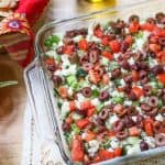 Greek Layer Dip presented in a glass container surrounded by tortilla chips and bright red tomato