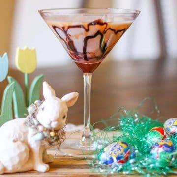Cadbury Creme Egg Martini next to cadbury creme eggs and a porcelain bunny