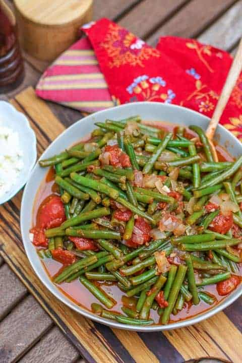 green beans in a bowl on wooden cutting board