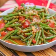 Greek Green Beans (Fasolakia) in grey bowl on a wooden cutting board