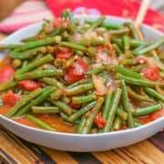 Greek Green Beans (Fasolakia) in grey bowl on a wooden cutting board