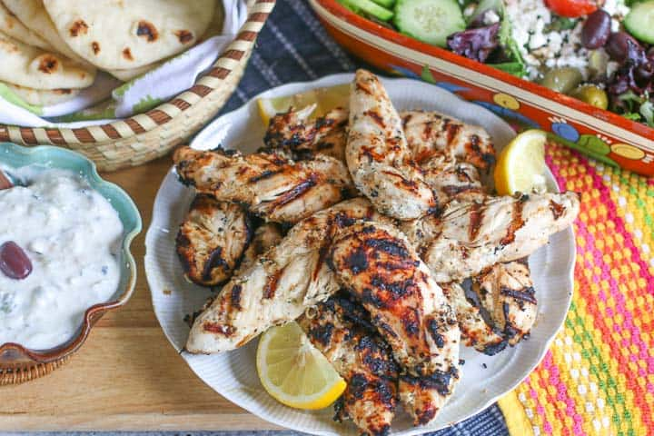 Grilled Greek chicken on a white plate with slices of lemon for garnish. A bowl of tzatziki sauce and pita are arranged to the side.