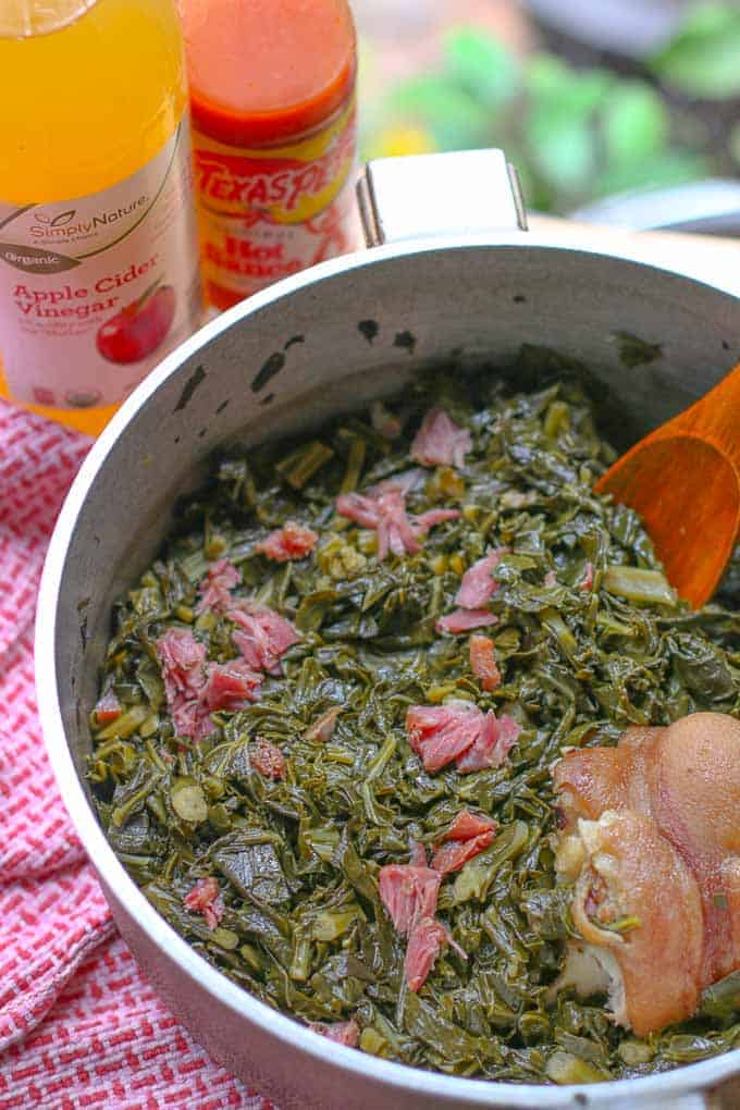 cooked collard greens in a large pot with ham hock