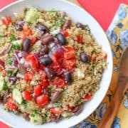Mediterranean Quinoa Salad in white bowl with a wooden spoon next to it.