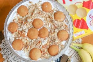 Banana Pudding in glass bowl with a box of vanilla wafers and bananas to the side