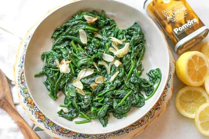 Sauteed spinach on a plate surrounded with fresh lemons and Pomora Olive Oil