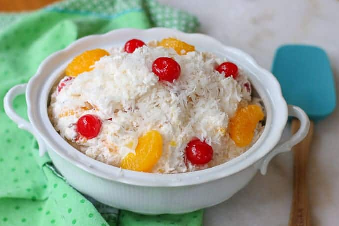 fruit salad with coconut and cherries on top