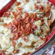 fried cabbage in red bowl with wooden spoon