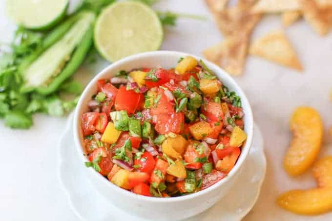 Peach salsa surrounded by peaches, chips, and jalapeno
