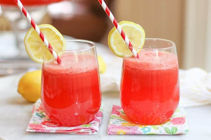 Two glasses of strawberry lemonade punch with a slice of lemon and red and white straws.