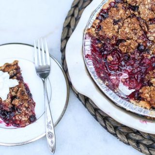slice of mixed berry pie on a plate with a pie to the side