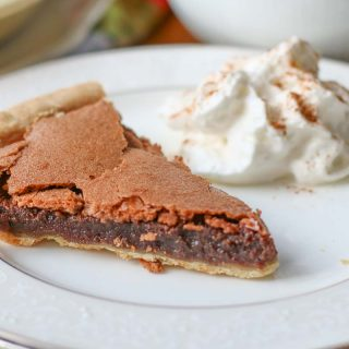 Chocolate Chess Pie with a side of whipped cream on a white plate.