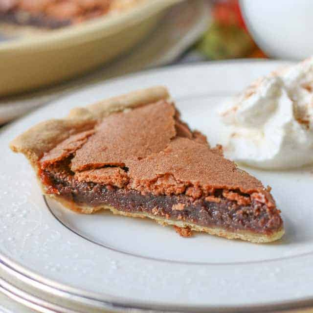 slice of chocolate pie on white plate with a side of whipped cream