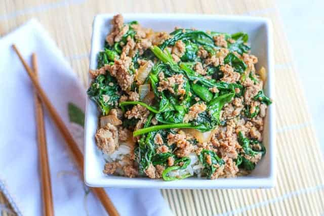 Turkey Spinach Stir Fry in white square dish with chop sticks