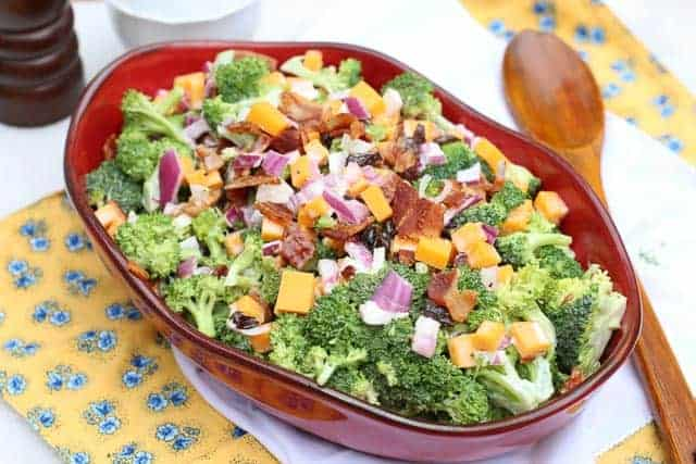 broccoli bacon salad in a red bowl on white linen with wooden spoon next to it