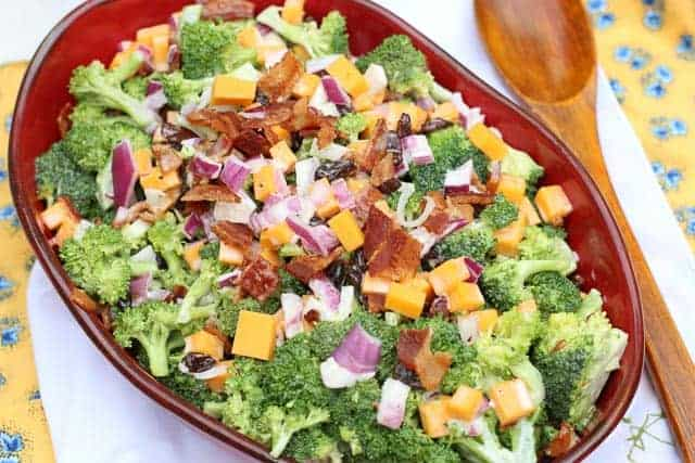 broccoli salad in red bowl with wooden spoon