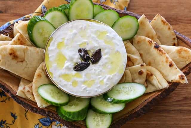tzatziki sauce in a bowl surrounded by cucumbers and pita bread