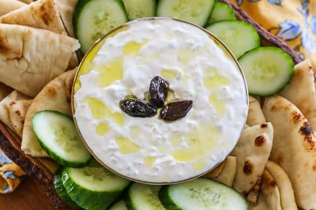 cucumber sauce in a bowl with olives on tip surrounded by cucumbers and pita bread