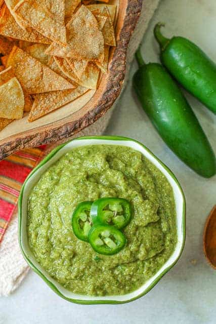 Mexican green sauce in a bowl with slices of jalapenos on top, two jalapenos to the side, and a bowl of tortilla chips in the background