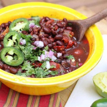 Mexican Black Beans in a yellow bowl on a red napkin. Cut limes are placed beside the yellow bowl.