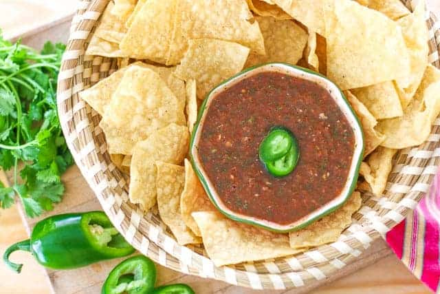 red salsa in a bowl surrounded by tortilla chips