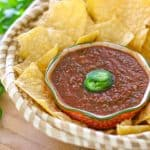 homemade salsa in a bowl surrounded by tortilla chips on a wooden block with jalapeno and cilantro to the side