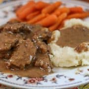 Country Style Steak with carrots and mashed potatoes on a white plate