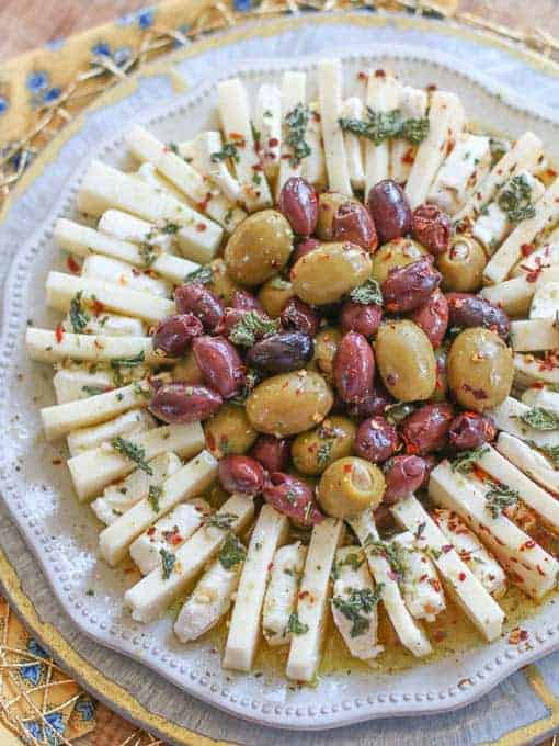 cheese and olives centered on a round white platter with a bright yellow napkin to the side