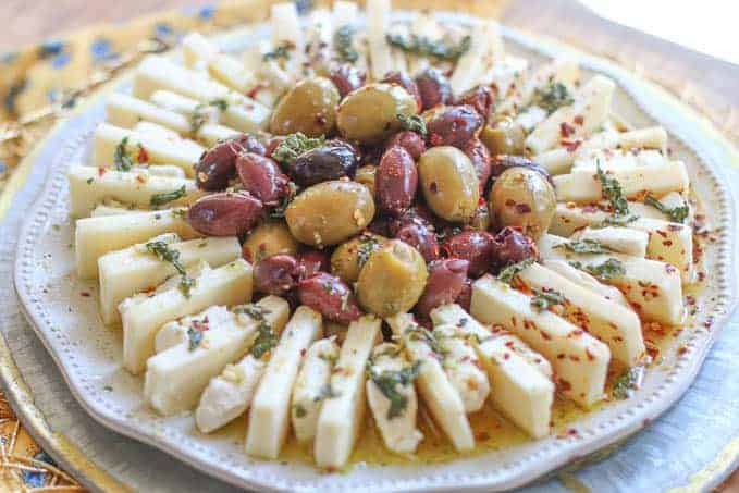 cheese and olives marinating in dressing on a white platter