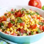 Bring summer to your table with this simple garden fresh Summer Corn Salad. Vibrant mixtures of tomatoes, basil, corn, and dressing create a pleasing side salad to any meal. #corn #salad