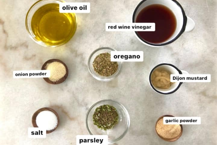 Ingredients for Greek salad dressing: olive oil, red wine vinegar, dijon mustard, oregano, parsley, onion powder, garlic powder, salt