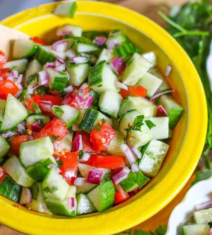 Israeli Salad in yellow bowl with wooden spoon to the side