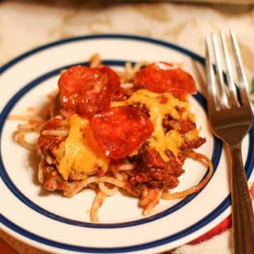 baked spaghetti on a plate with a fork to the side