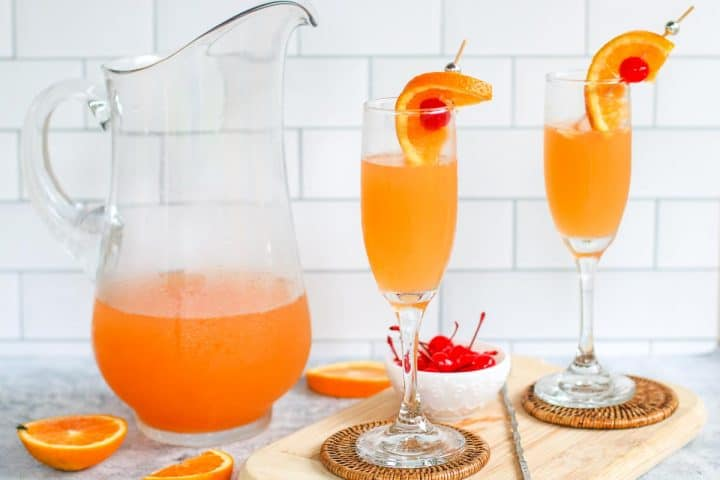 champagne punch in a glass pitcher with 2 glasses of champagne punch to the side