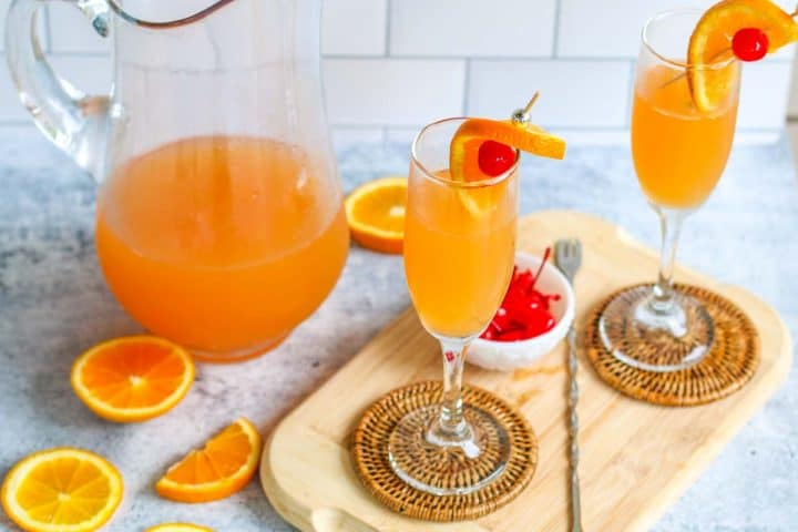 2 champagne punch glasses on a wooden board next to a pitcher of champagne punch. orange slices and a bowl of cherries are to the side.
