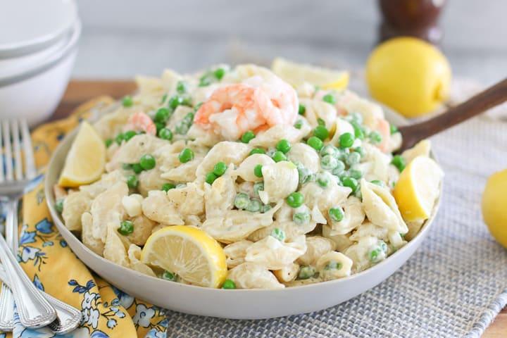 creamy shrimp shell pasta in grey bowl garnished with lemons on grey dinner mat