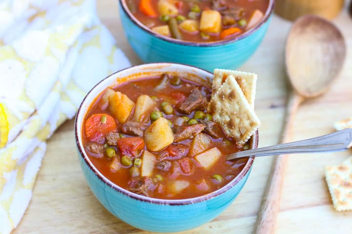 vegetable beef soup in blue bowl with crackers on the side