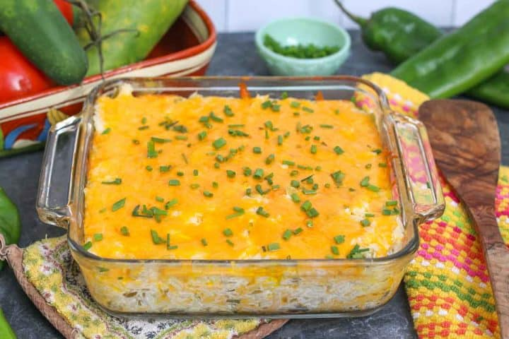 Green chile casserole in a glass baking dish on pot holder with green hatch chiles to the side in the back ground