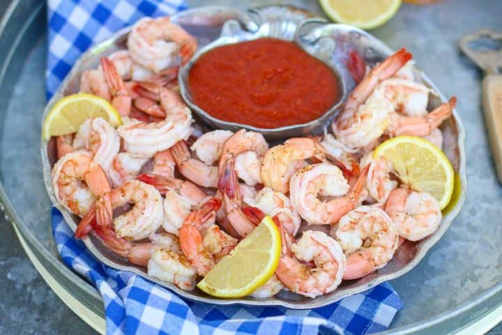 a checkered blue towel wit a silver platter topped with boiled shrimp and cocktail sauce. The shrimp cocktail is garnished with lemon slices