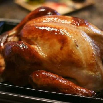 turkey cooked perfectly in the oven on a metal roasting dish.