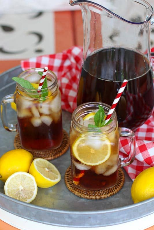 Two glasses of iced tea next to a pitcher of tea on a metal tray