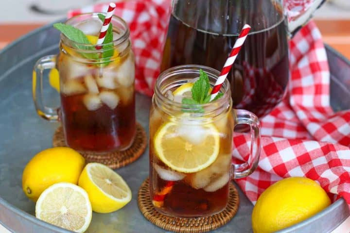 Two glasses of sweet tea on a metal tray with lemons to the side next to a red and white checkered cloth with a pitcher of tea set on top of it.