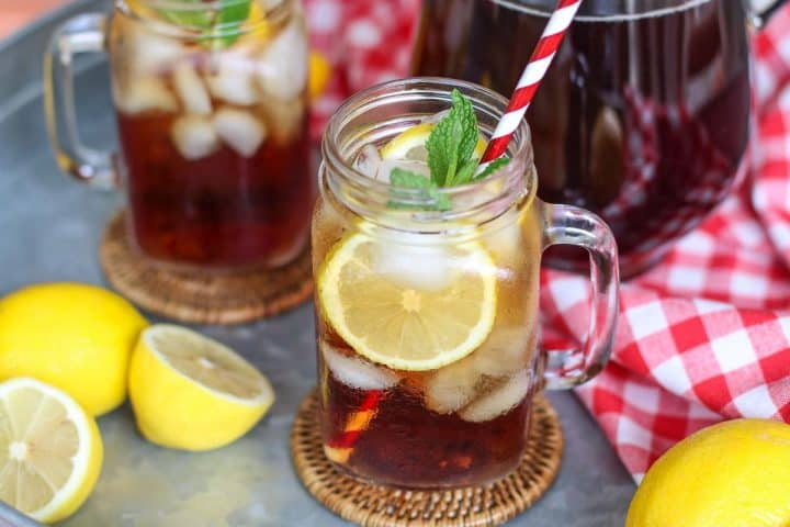 glass of iced tea with lemons to the side and a glass of tea in the background