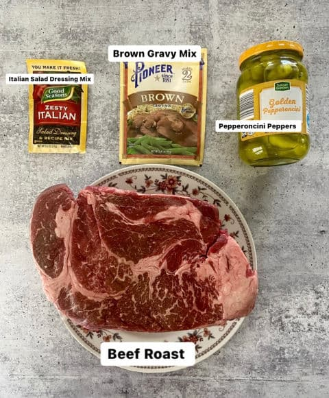 ingredients for Crock-Pot Pepperoncini Pot Roast: Italian salad dressing mix, brown gravy mix, pepperoncini peppers, and beef roast